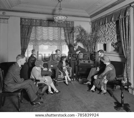 Group of men and women listening to a radio in the Hamilton Hotel, Washington, D.C. The Atwater Kent radio features an enclosed speaker at the top of the cabinet. The photo was associated with Thomas