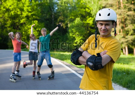 Group of men and women on rollerblades having fun at park