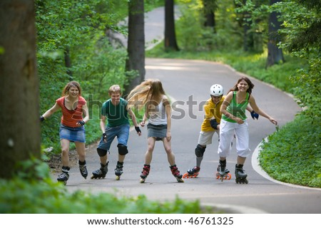 Group of men and women on rollerblades skating at park - stock photo
