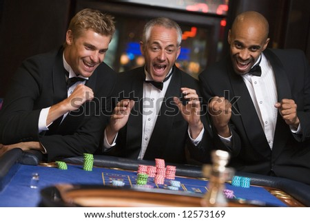 Group of men celebrating win at roulette table in casino