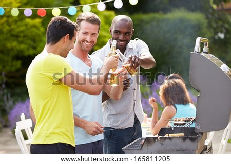 Group Of Men Cooking On Barbeque At Home - stock photo