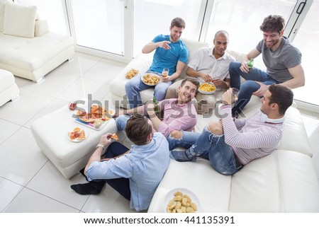 Group of men sat at home enjoying pizza and beer. - stock photo