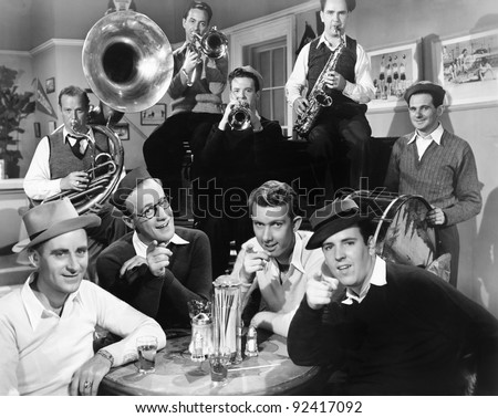 Group of men sitting in a diner with musicians behind them - stock photo