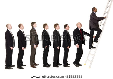 Group of men standing in line to climb a ladder - stock photo