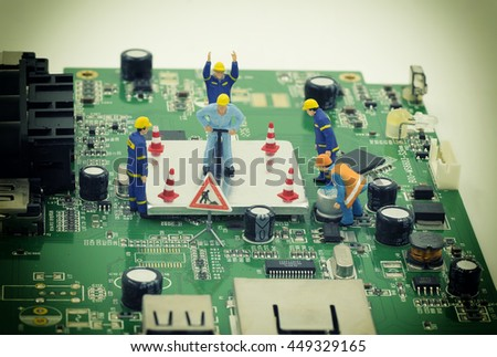 group of mini workers are try to repair a chip on mainboard with vintage filter - can use to display or montage on product or concept of on process to fix - stock photo