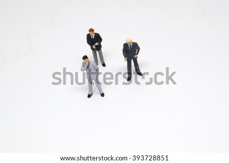 Group of miniature business people figure in white background