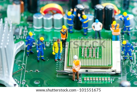 Group of miniature engineers inspecting computer processor - stock photo