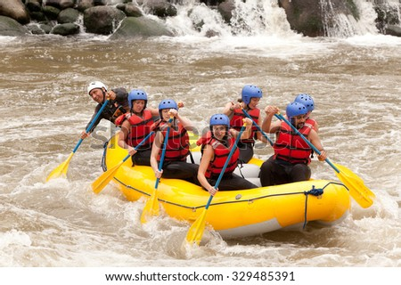 Group Of Mixed Tourist Men And Women With Guided By Professional Pilot On Whitewater River Rafting In Ecuador