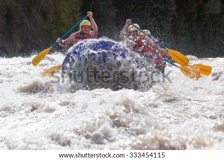 Group Of Mixed Tourist Men And Women With Guided By Professional Pilot On Whitewater River Rafting In Ecuador - stock photo