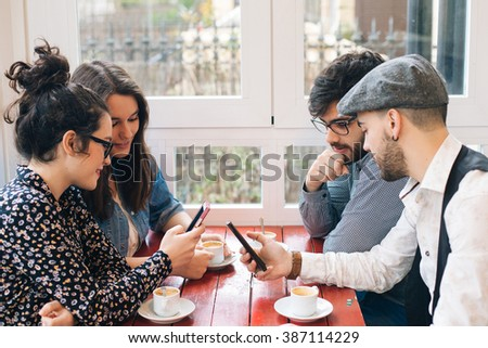 Group of modern friends using cellphones in a cafe - stock photo