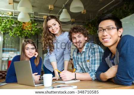 Group of modern happy excited businesspeople having a meeting and using laptop in conference room