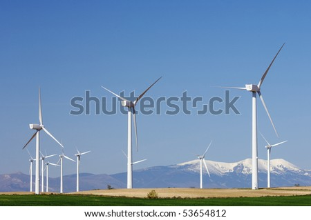 group of modern windmills and in the background snowy mountains