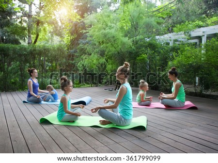 Group of mothers and daughters doing exercise practicing yoga outdoors. Healthy lifestyle