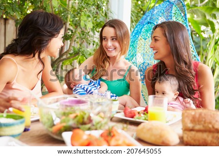 Group Of Mothers With Babies Enjoying Outdoor Meal At Home - stock photo