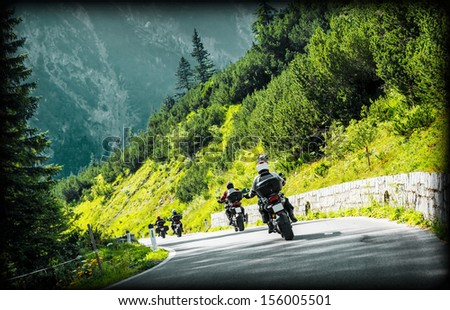 Group of moto bikers on mountainous highway, riding on curve road pass across Alpine mountains, extreme lifestyle, freedom concept - stock photo