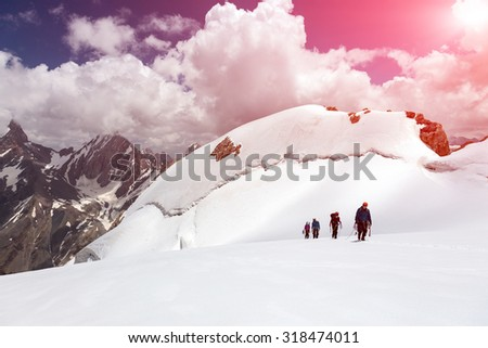 Group of Mountaineers Walking on Ice Field Four Members Team Sport Clothing Going Climbing Gear Up  Mountain Peaks Blue Sky Majestic Summits Shining Sun Background Himalaya - stock photo