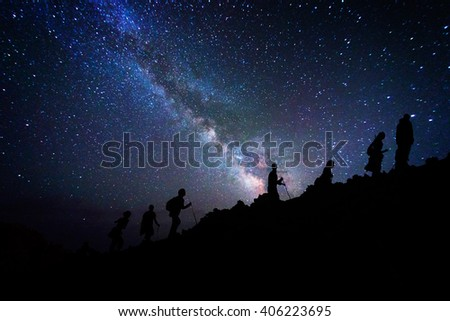 Group of mountaineers who climb the mountain top under the milky way - stock photo
