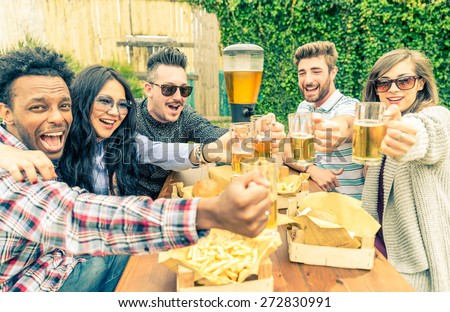 Group of mult-ethnic friends toasting beer glasses - Happy people partying and eating in home garden - Young active adults in a picnic area with burgers and drinks - stock photo
