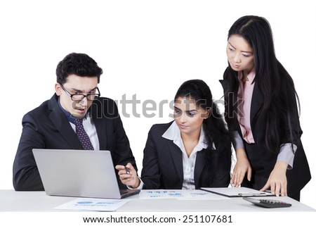 Group of multi-ethnic businesspeople discussing a job with laptop computer on desk - stock photo