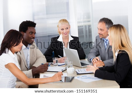Group Of Multi Ethnic Businesspeople Discussing Together In Office - stock photo