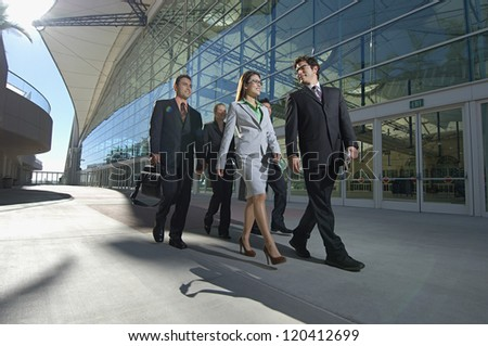 Group of multi ethnic businesspeople walking past office building - stock photo