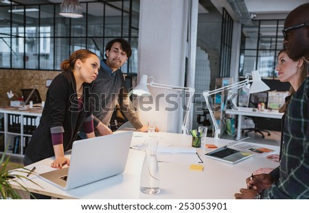 Group of multi ethnic creative people discussing during a meeting. Team of executives meeting around a table
