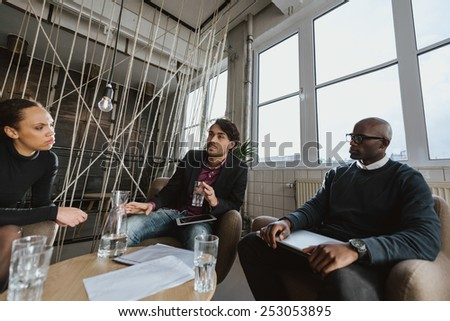 Group of multi ethnic executives discussing during a meeting in office lobby. Business people brainstorming ideas. - stock photo