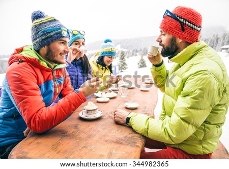 Group of multi-ethnic friends drinking hot chocolate and coffee - Happy people partying and eating in home garden - Young active adults in a restaurant on winter vacation - stock photo