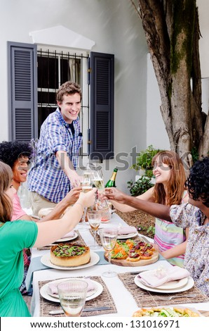 Group of multi ethnic friends having fun celebrating toasting with champagne at an outdoor garden party - stock photo