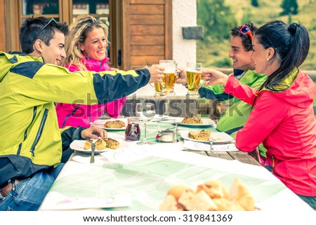 Group of multi-ethnic friends toasting beer glasses - Happy people partying and eating in home garden - Young active adults in a restaurant on winter vacation - stock photo