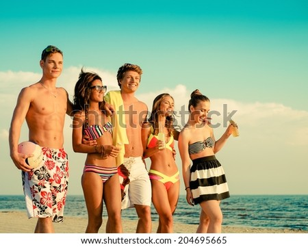 Group of multi ethnic friends walking on a beach - stock photo