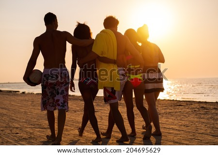 Group of multi ethnic friends walking on a beach against sunset  - stock photo