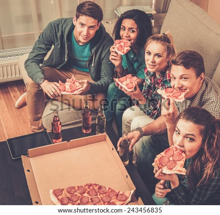 Group of multi-ethnic friends with pizza and bottles of drinks having party - stock photo