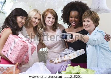 Group of multi ethnic people taking self portrait through digital camera at party - stock photo