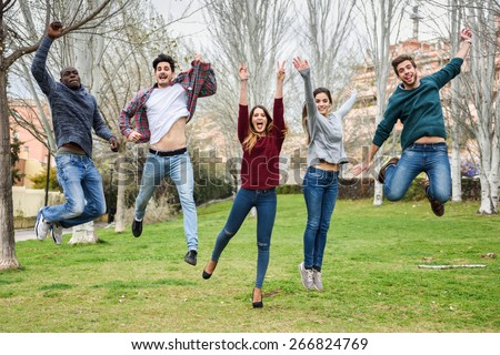 Group of multi-ethnic young people jumping together outdoors - stock photo