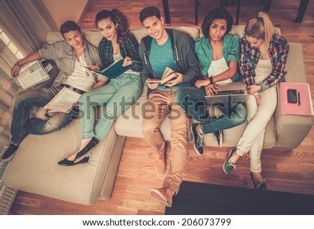 Group of multi ethnic young students preparing for exams in home interior  - stock photo