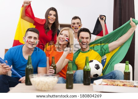 Group of multi national football fans cheering  - stock photo