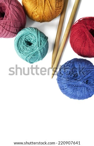 Group of multicolor balls of yarn and pair wooden knitting needles over white