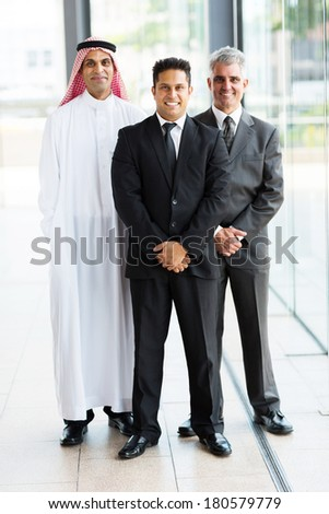 group of multicultural businessmen standing in modern office - stock photo