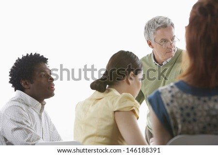 Group of multiethnic business colleagues at office meeting against white background - stock photo