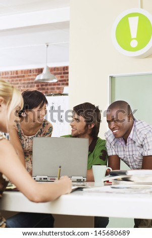 Group of multiethnic business people using laptop in meeting room - stock photo