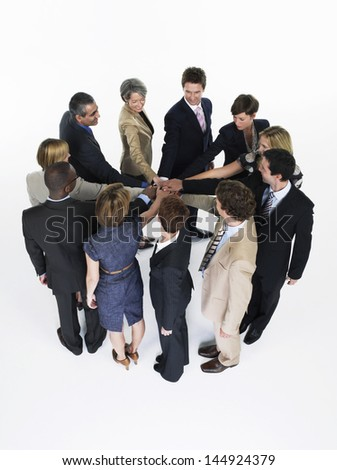 Group of multiethnic businesspeople joining hands in a circle against white background - stock photo