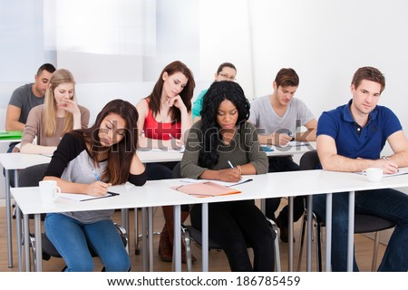 Group of multiethnic college students writing at desk in classroom - stock photo