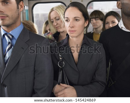 Group of multiethnic commuters standing in a train - stock photo