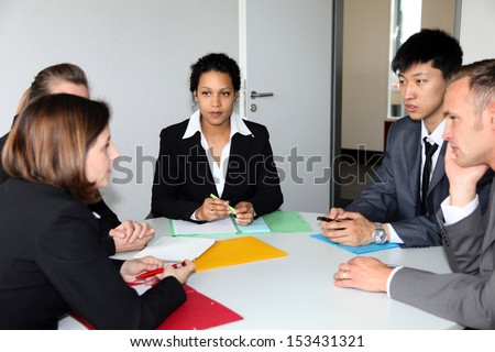 Group of multiethnic diverse young business people in a meeting sitting around a table with serious expressions discussing a new strategy or solution to a problem - stock photo