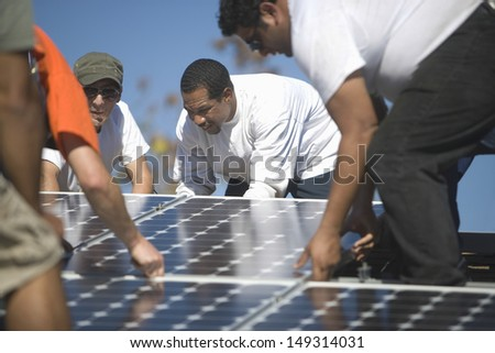 Group of multiethnic engineers placing solar panel on rooftop - stock photo