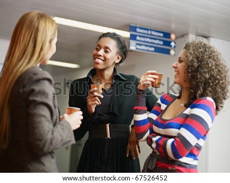 group of multiethnic female colleagues drinking coffee and tea. Horizontal shape, waist up - stock photo
