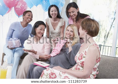Group of multiethnic female friends attending baby shower - stock photo
