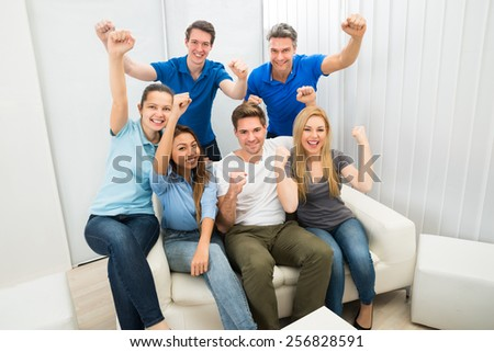 Group Of Multiethnic Friends Cheering Sitting On Couch