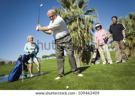 Group of multiethnic friends playing golf at golf course